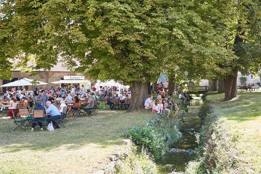 Unter grün belaubten Bäumen sitzen feiernde Menschen im Freizeitlook, das Event findet im Park von Rittergut Lucklum statt