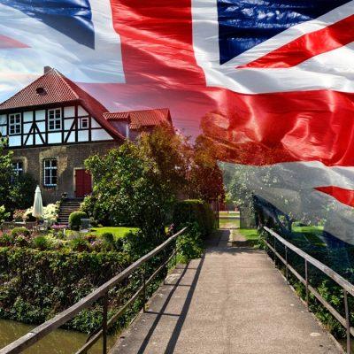 Über eine Brücke gehend sieht man links das Herrenhaus vom Rittergut Remeringhausen, den Hintergrund bildet eine englische Flagge
