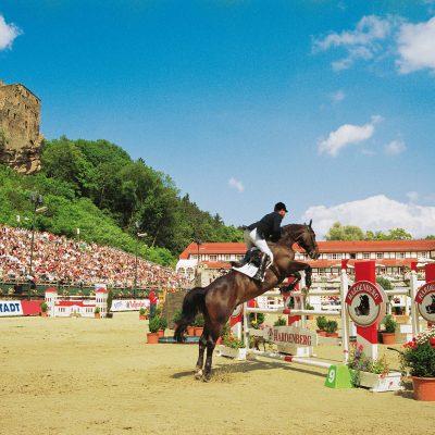 Springreiter mit Pferd vor einem Hindernis beim Hardenberg Burgturnier