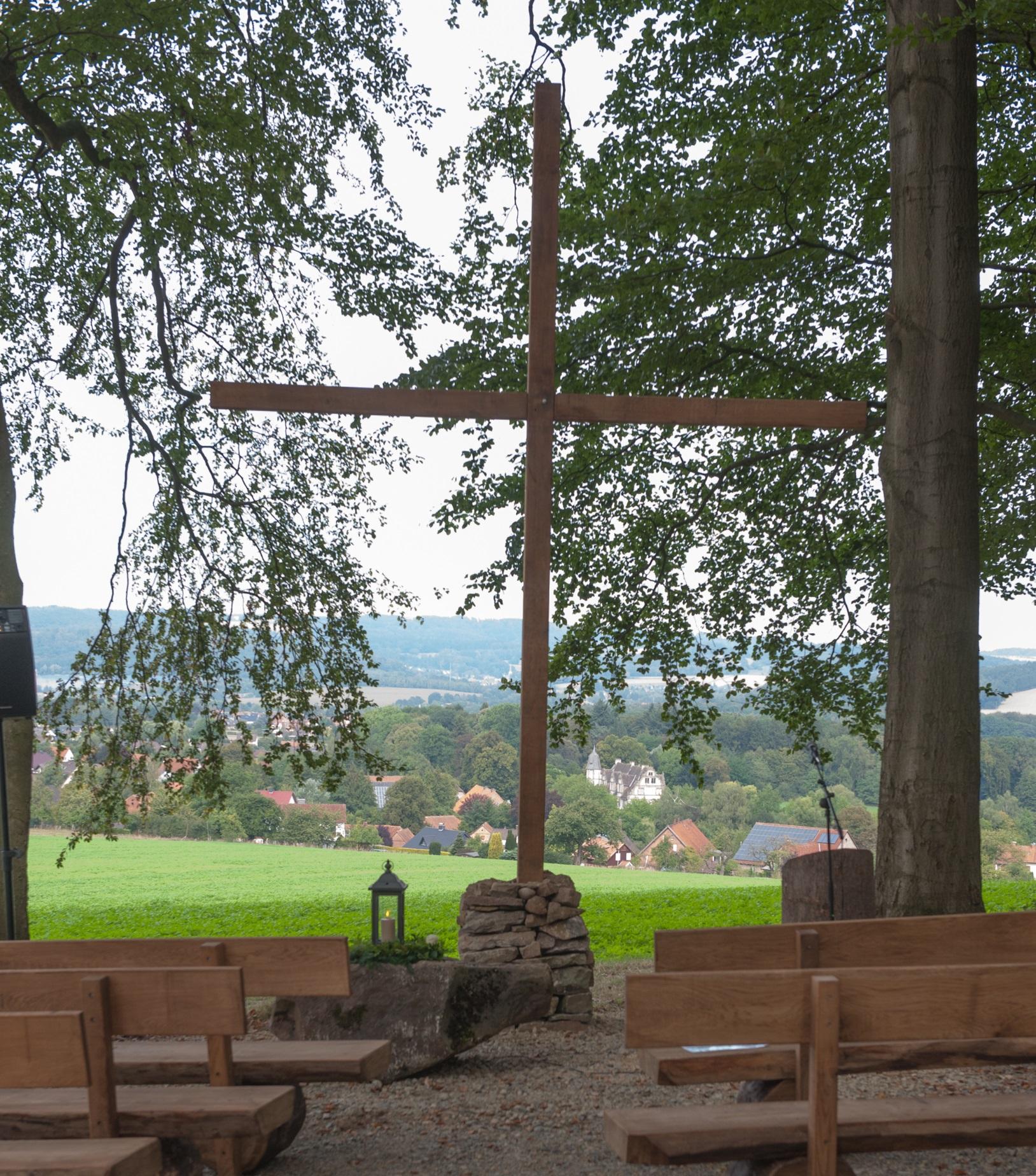 Links und rechts zwei hölzerne Bankreihen mit Blick auf ein Holzkreuz, der Platz für eine Andacht. Im Hintergrund unten ist wieder das Schloss Wendlinghausen zu erkennen
