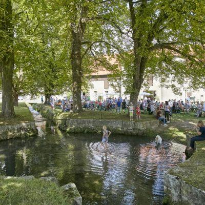 Spielende Kinder am Teich, im Hintergrund sitzen Menschen an Bierzelttischen, alles im Großen Wirtschaftshof von Rittergut Lucklum