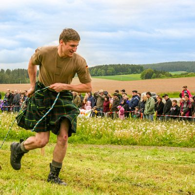Auf einer Wiese steht ein Teilnehmer der Highland Games